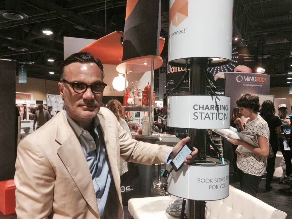Celebrity stylist and salon owner Jonathan Antin charges his Smartphone at the clever charging station in MINDBODY's booth at ISSE.
