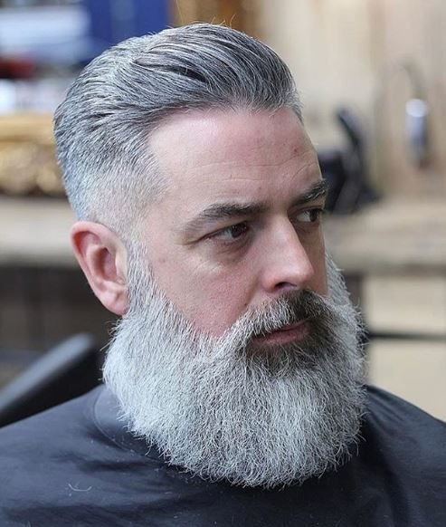 Embracing silver is trending in hair color, so it makes sense we'd see it in men's cuts, as well. @tomchapman_tcxhd crafted a well groomed beard and style that redefines silver fox.