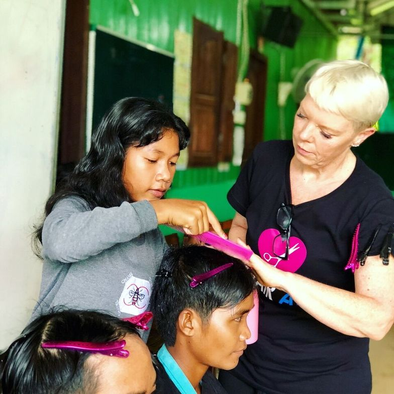 Tabatha Coffey teaches haircutting techniques in Cambodia while volunteering with Hair Aid.