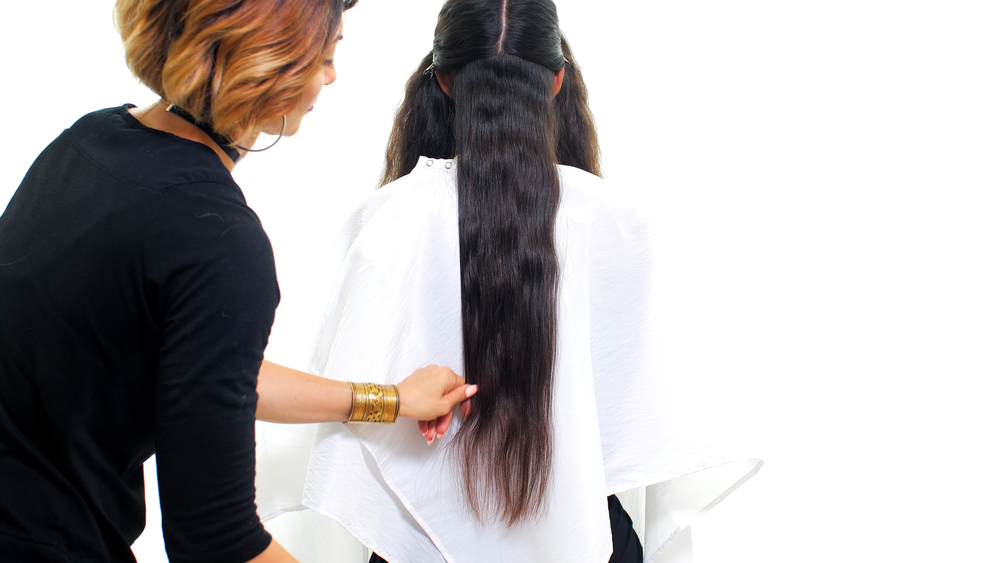 STEP 2A: Part from center hairline to the nape of the neck, creating left and right sections. Then part each side horizontally from ear to ear, at the occipital. Clip away the front sections. Comb the back bottom sections straight down, and establish the perimeter length with a shallow point cutting technique to create softness. Continue by taking horizontal sections around the entire head until you finish cutting the perimeter.
