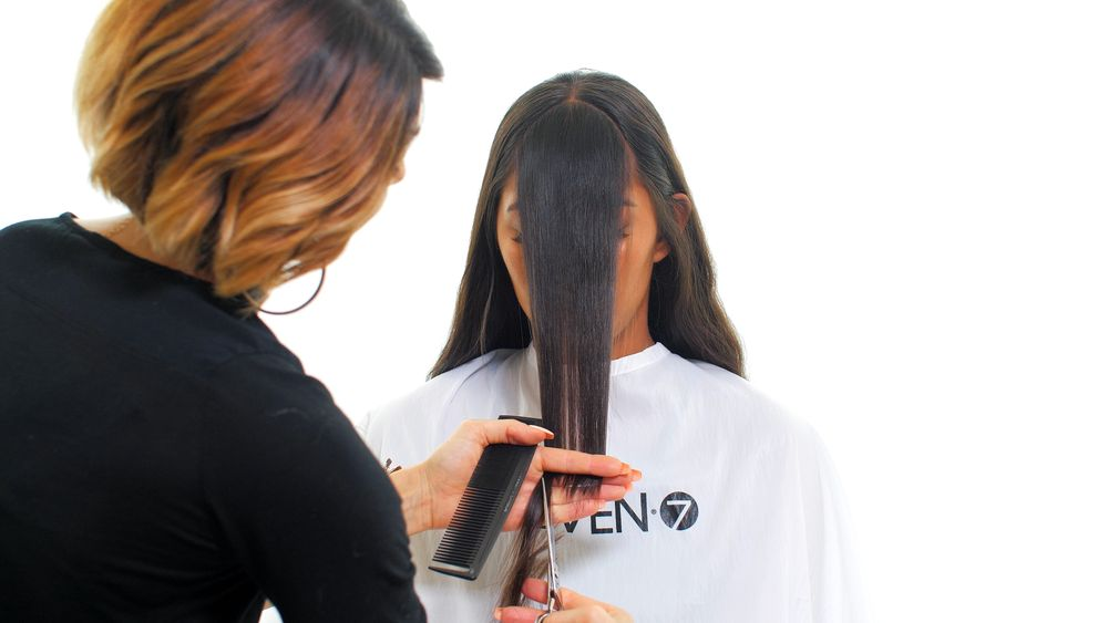 STEP 3: Take a triangular section from the center part to the end of each brow. You can take a smaller or larger section depending on the desired amount of fringe. Comb down with light tension, and point cut to desired length. Adjust the depth of your point cutting to achieve more or less texture.