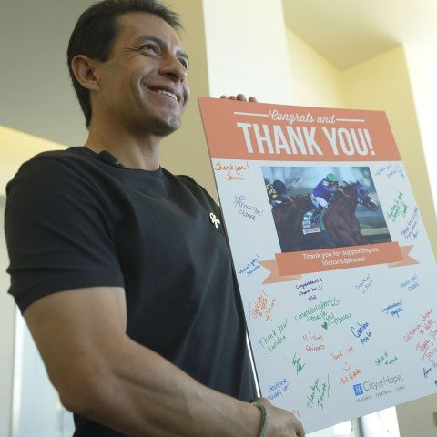 Jockey Victor Espinoza, a supporter of City of Hope, shows a signed card of support from patients during a recent visit.