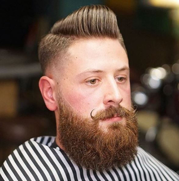 This look from @vinnycleancuts has clean lines without losing any fun. The hair contrasts with the full beard and curled moustache to create a cohesive overall style.