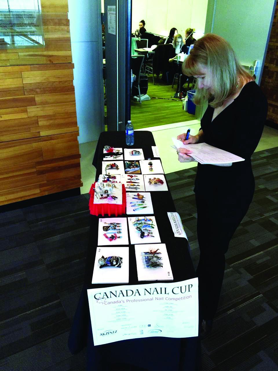 <p>A judge scores nail art at the Canada Nail Cup.</p>