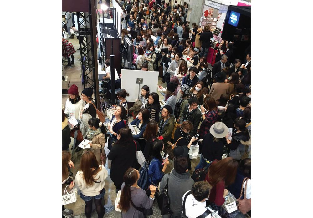 <p>At the Tokyo Nail Forum, crowds of people watch a demo from behind the stage on the TV while others stand in line to purchase products. Photo courtesy @HiJeanJean</p>