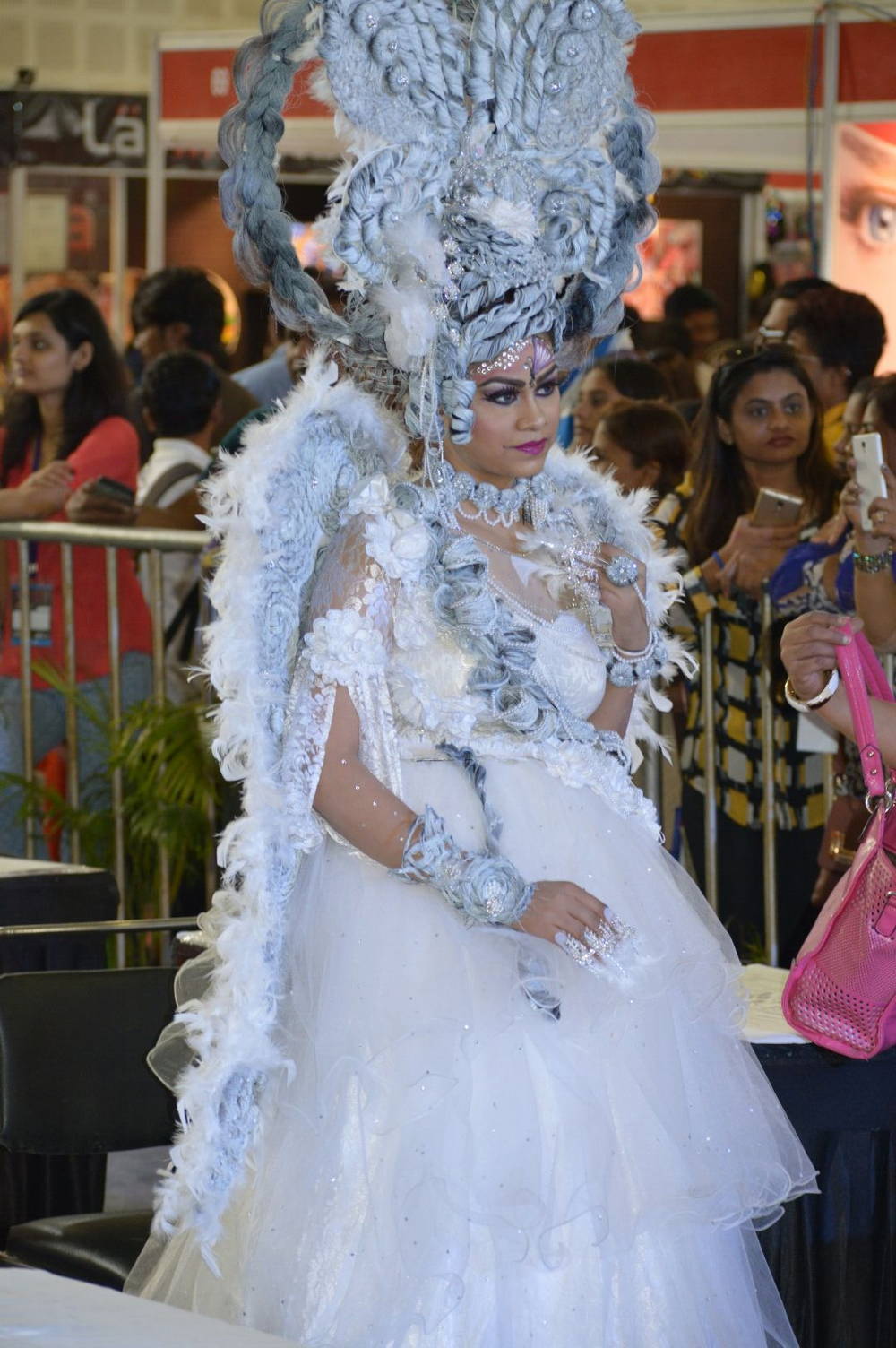 <p>A model adorned in white walks the runway at an AIHBA event.</p>