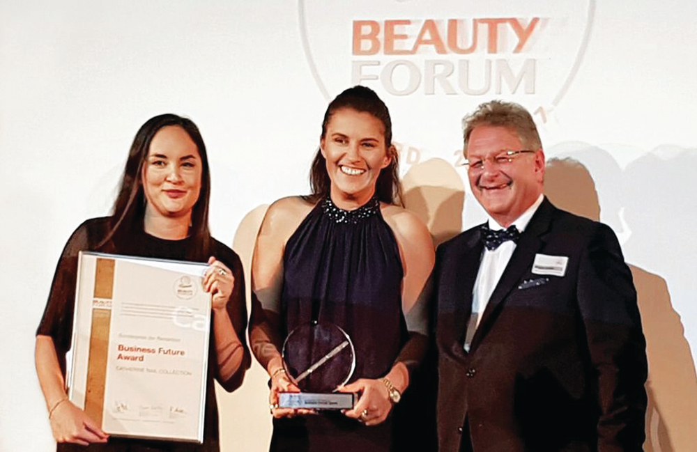 <p>Catherine Frimmel (center) accepts an award on behalf of Catherine Nail Collection at a Beauty Forum ceremony.</p>