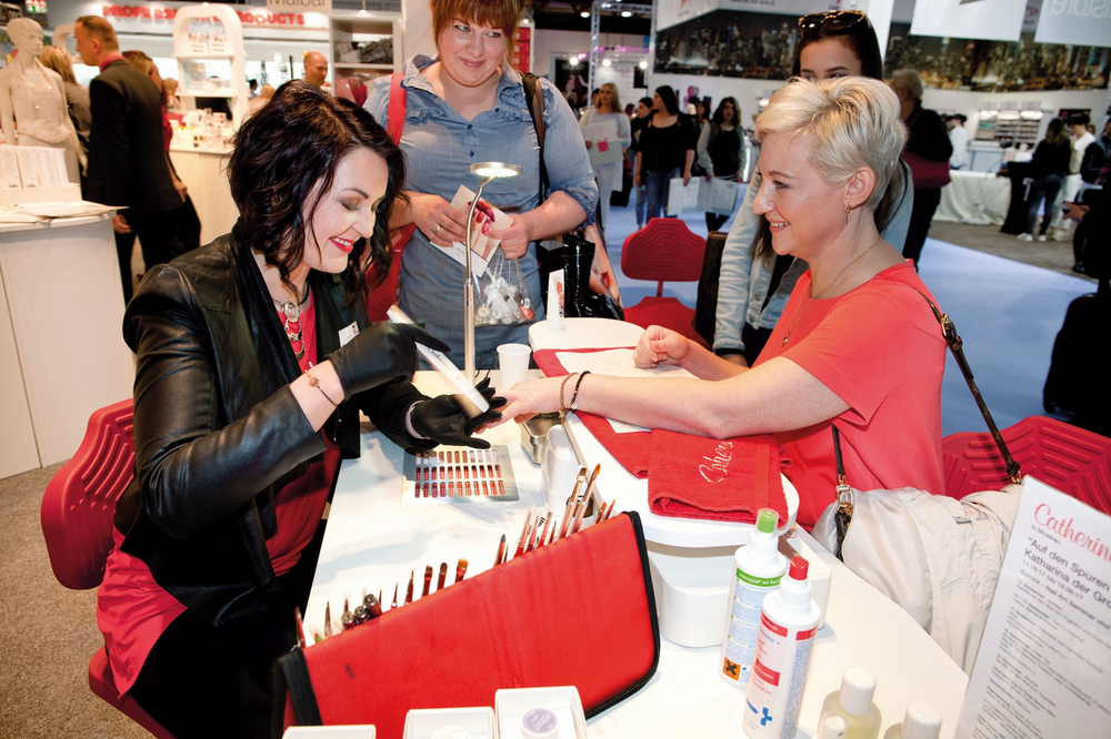 <p>A nail designer demonstrates Catherine Nail Collection products on the tradeshow floor.</p>