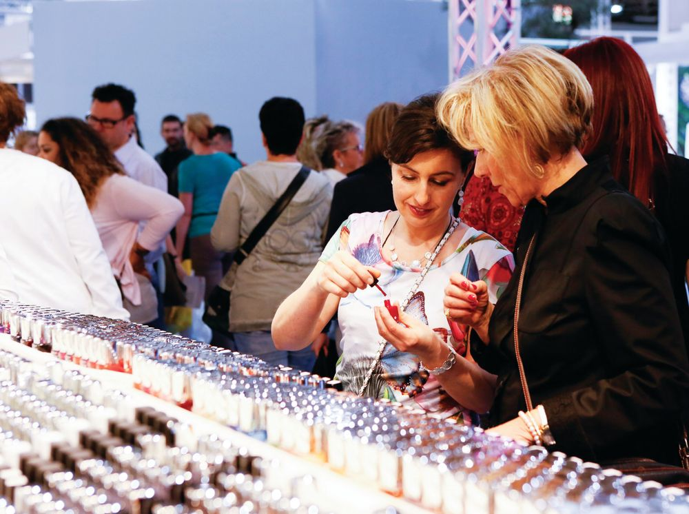 <p>At Beauty Düsseldorf, two attendees admire a classic red polish. Photo courtesy Messe Düsseldorf / Constanze Tillmann.</p>