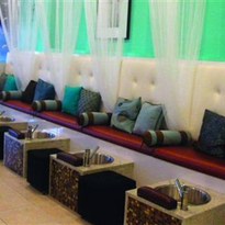 The brown and white pedicure bench runs along one wall, separated by sheer white curtains and...