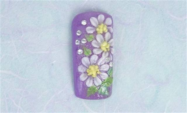 <p><strong>April (birth flower: daisy; birthstone: diamond)</strong></p> <p>1. Apply Amethyst for the background. Add Breakin the Bank down the center of the nail. Cap with clear. File and finish the nail.</p> <p>2. Apply Competition White to create the daisy petals. Apply small dots of Citrine to create the flower centers. Wet brush Voodoo over the centers for depth and definition.</p> <p>3. Double dip (using two colors on the brush at once) Emerald and Peridot to create the leaves.</p> <p>4. Apply six clear rhinestones. Apply UV 30 and Never Yellow Sealer.</p>