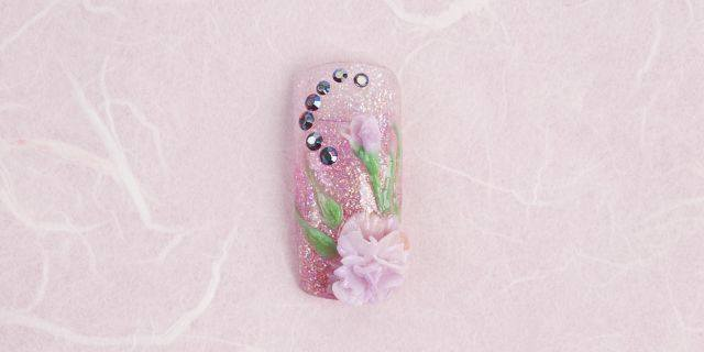 <p><strong>January (birth flower: carnation; birthstone: garnet)</strong></p> <p>1. Fade the background on a curve using Raspberry Crème, Bubble Gum, and Show Me Your Beads.</p> <p>2. Double dip (using two colors on the brush at once) random combinations of Sweet Pea, Pansy, and Tourmaline. To form the carnation, place the first round of petals directly on the nail; remember to ruffle the outer edge of the petal. Continue to build the petals around and use your brush to pull up on the petals to give them dimension. If desired, you can build the petals on a form and attach them to the nail. Place the flower and bud.</p> <p>3. Peridot and Emerald create the stem and leaves. Use deep red garnet colored rhinestones. Apply top coat.</p>