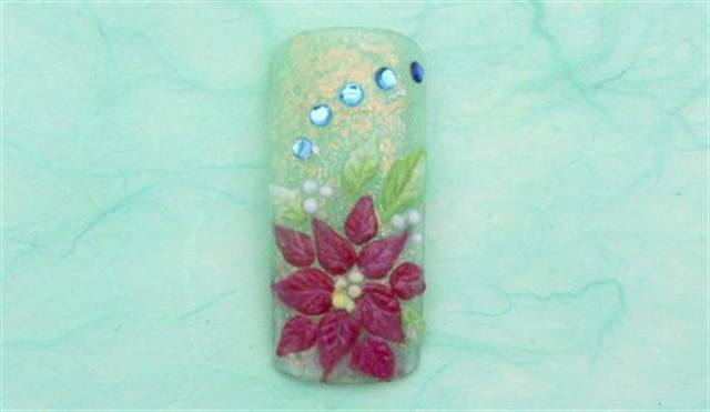 <p><strong>December (birth flower: poinsettia/holly; birthstone: blue topaz)</strong></p> <p>1. Fade the background using Sour Apple and Cocktail Time. </p> <p>2. Use Ruby to create the petals. Use the flat side of your brush to draw lines in the petals. Using Truly White, brush over the lines so they are highlighted by the white. Double dip (using two colors on the brush at once) dots of Citrine and Truly White to build centers.</p> <p>3. Double dip Emerald and Truly White for the leaves. Apply blue topaz-colored rhinestones. Apply top coat.</p>