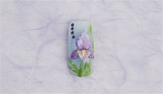 <p><strong>February (birth flower: iris; birthstone: amethyst)</strong></p> <p>1. Fade the background diagonally using Italian Ice and Grand Parade, then Italian Ice again.</p> <p>2. Build two iris background petals directly on the nail. Double dip (using two colors on the brush at once) using Petunia and Amethyst; make the petals curve out from the center. Using the same colors, build two petals curving downward from the center. Again using Petunia and Amethyst on a nail form build the center petal and a bottom petal, curve the form until the acrylic dries to create the definition. Apply to the nail.</p> <p>3. Use Citrine for centers, and Peridot and Voodoo used for leaves. Apply amethyst colored rhinestones. Apply top coat.</p>