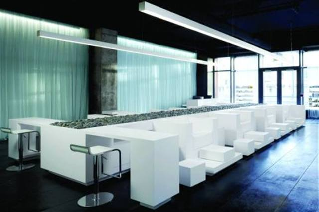 """You don't need a lot of color to make a splash with your salon design. Try a more subdued palette, like the one shown here at Mizu Spa in San Francisco, to welcome clients to a calm sanctuary. Mizu (which means """"water"""" in Japanese) features a shimmery, pale blue curtain to separate the space, pure white pedicure chairs, and an aisle of river rocks that adds interest. """"All of the decisions are though of in terms of creating th refreshing, tranquil, and purifying atmosphere of water,"""" says Stanley Saitowitz of Stanley Saitowitz/Natoma Architects. less can be more when it comes to design; you don't necessarily have to be loud to be unique."""