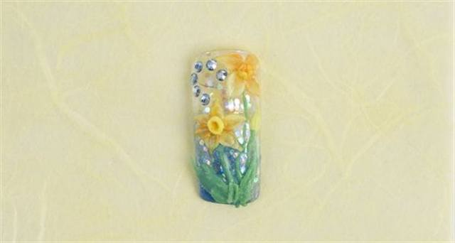 <p><strong>March (birth flower: daffodil; birthstone: aquamarine)</strong></p> <p>1. Fade the background using Grand Parade, and Clear with Quartz Precious Gems.</p> <p>2. Double dip (using two colors on the brush at once) using Citrine and Daffodil build the daffodils by pulling petals out from center of flower. To place the flower center, drop a drier ball of Daffodil, then with the sharp point of your brush push a hole into the center and pull up on the outside edge. Continue to do this until the acrylic dries and the center holds its shape. </p> <p>3. Using Emerald and Peridot with Voodoo for depth create leaves. Apply aquamarine colored rhinestones. Apply top coat.</p>