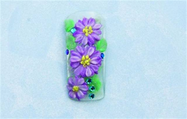 <p><strong>September (birth flower: aster; birthstone: sapphire)</strong></p> <p>1. Double dip (using two colors on the brush at once) Silver and Peridot to build leaves onto a clear nail. Cap with clear acrylic. File and finish the nail.</p> <p>2. Using Amethyst, build the first round of flower petals. Let dry, then stack a second round using Amethyst and Petunia double dipped. Double dip Silver and Peridot to add more leaves. Apply Citrine dots to create the flowers centers.</p> <p>3. Add sapphire rhinestones. Apply top coat.</p>