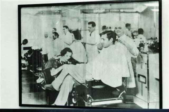 Clark Gable gets a manicure while getting his hair cut.
