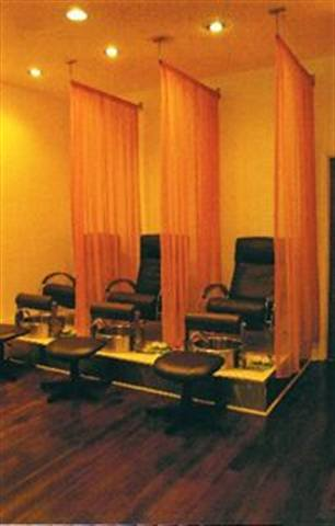 Honey Child Salon & Spa in Chicago uses warm-toned orange curtains toseparate the pedicure chairs and provide privacy in the massage area.