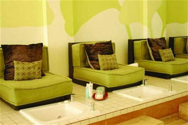 """Owner Kristin Luu of Fingers & Toes Nail Spa says that she wanted to create something fun with her salon. Behind the pedicure area is a mural featuring green ginkgo leaves and the leaf is in the salon's logo. Luu says she wanted something """"organic looking"""" so kept with the green furniture and color scheme throughout. The salon was even used in a movie scene in the movie """"Ocean's Twelve."""""""