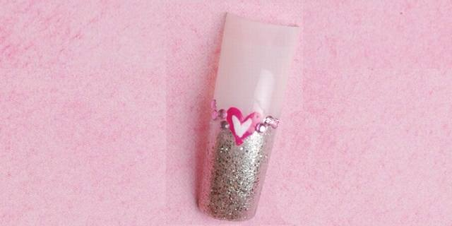 """<p align=""""left""""><strong>Rhinestones and Polish </strong></p> <p align=""""left"""">With a little bit of bling and a little bit of glitter, Muñoz hand-painted a heart in two shades of pink onto a tip, while also incorporating pink rhinestones. </p>"""