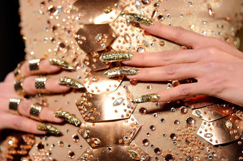 <p>Hand forged gold-looking paillettes adorned nails for The Blonds courtesy of CND.</p>