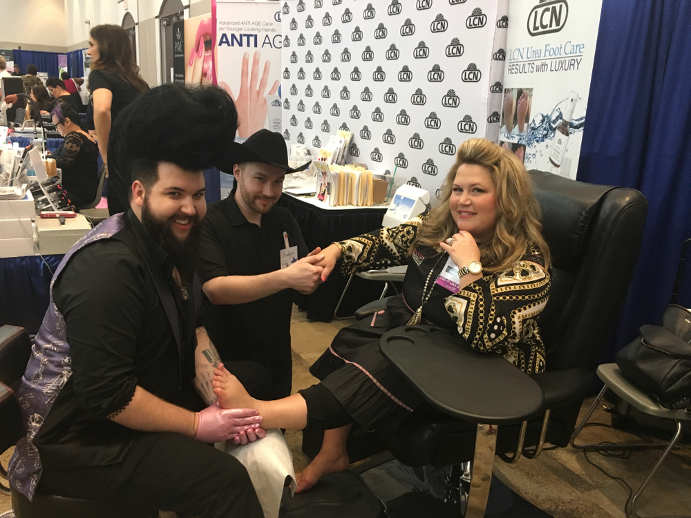 <p>Nellie Neal gave demos using a Belava chair at the LCN booth. Pro Tip Clips' Angela Blaisdell took him up on an offer to demo a service while Nail Talk Radio's Braden Jahr gave her some extra pampering on her hands.</p>