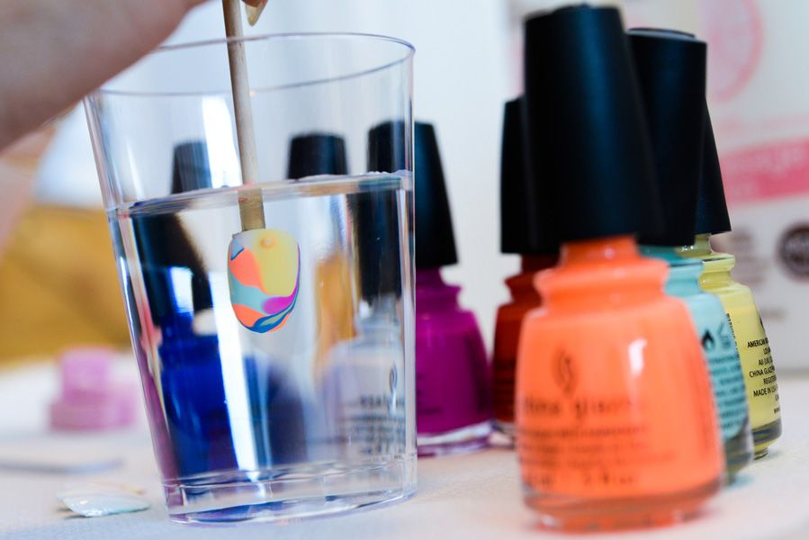 <p>To recreate the look from Degen, start with a foundation color, then add in three bright shades around the base color and draw lines with an orangewood stick. Dip nails in water vertically to avoid bubbles.Photo courtesy of Matthew Carasella/SocialShutterbug.com.&nbsp;</p>