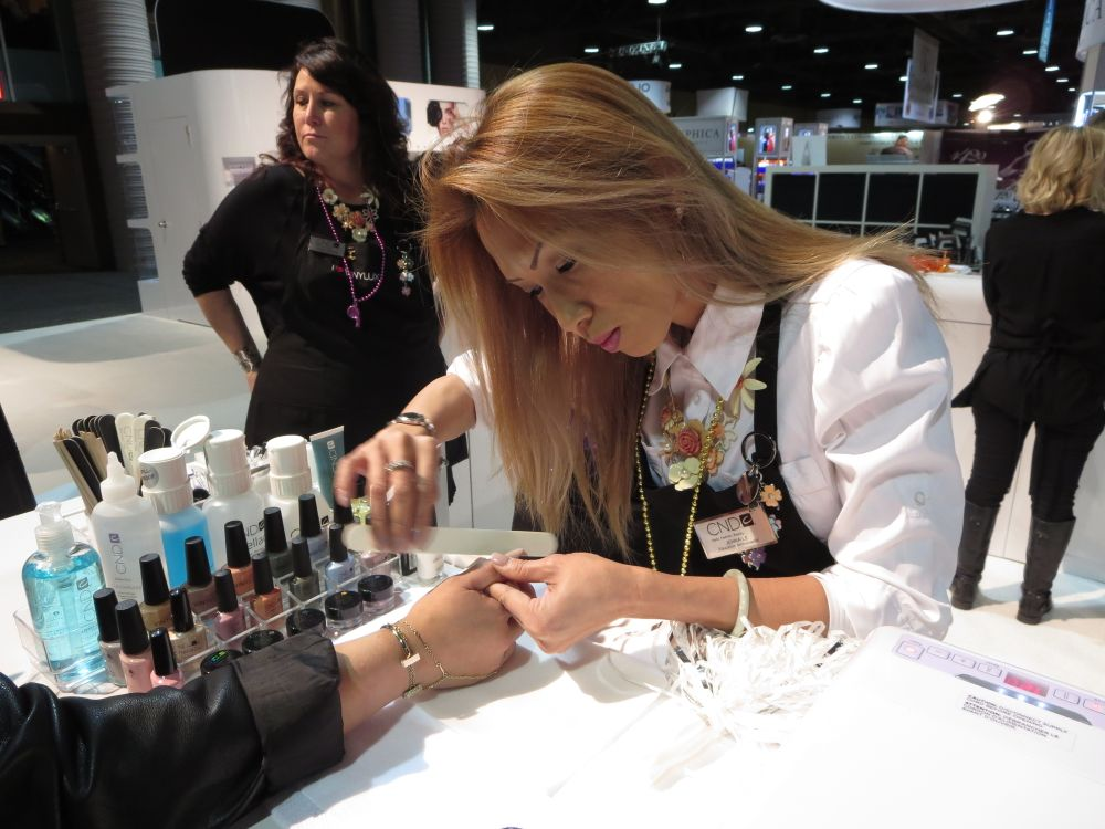 <p>At the CND booth, education ambassador Jenna Le demonstrates the sping line, Flaura &amp; Fauna.</p>