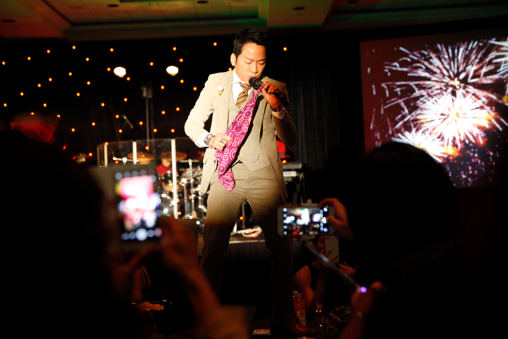 <p>Vietnamese singer Don Ho serenades the crowd from atop a table.</p>