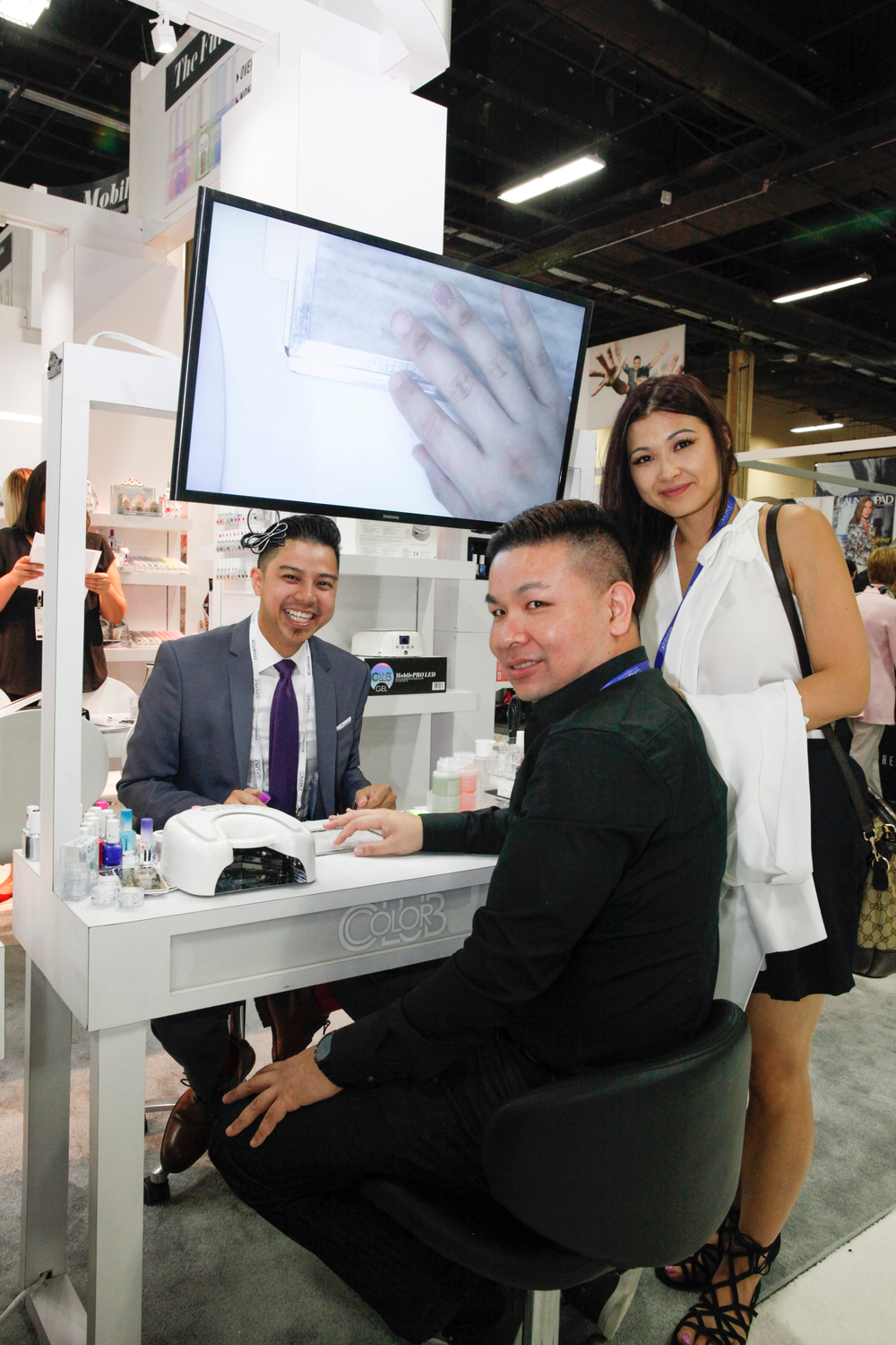 <p>Color Club's Robert Nguyen demos some of the company's newest products for Tuan Le and Jem Huynh from Jen Beauty Supply in Surrey, B.C.</p>