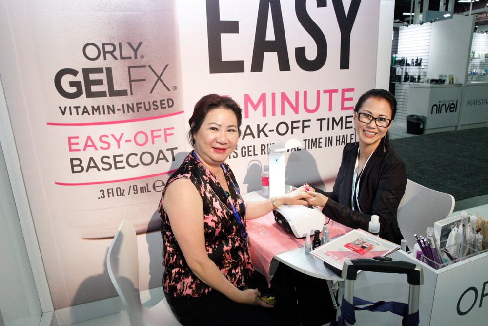 <p>Thu Tran from Phat Beauty Supply in San Diego, Calif., tries out Orly's newest Easy-Off Basecoat with Orly educator Trina Ngo</p>