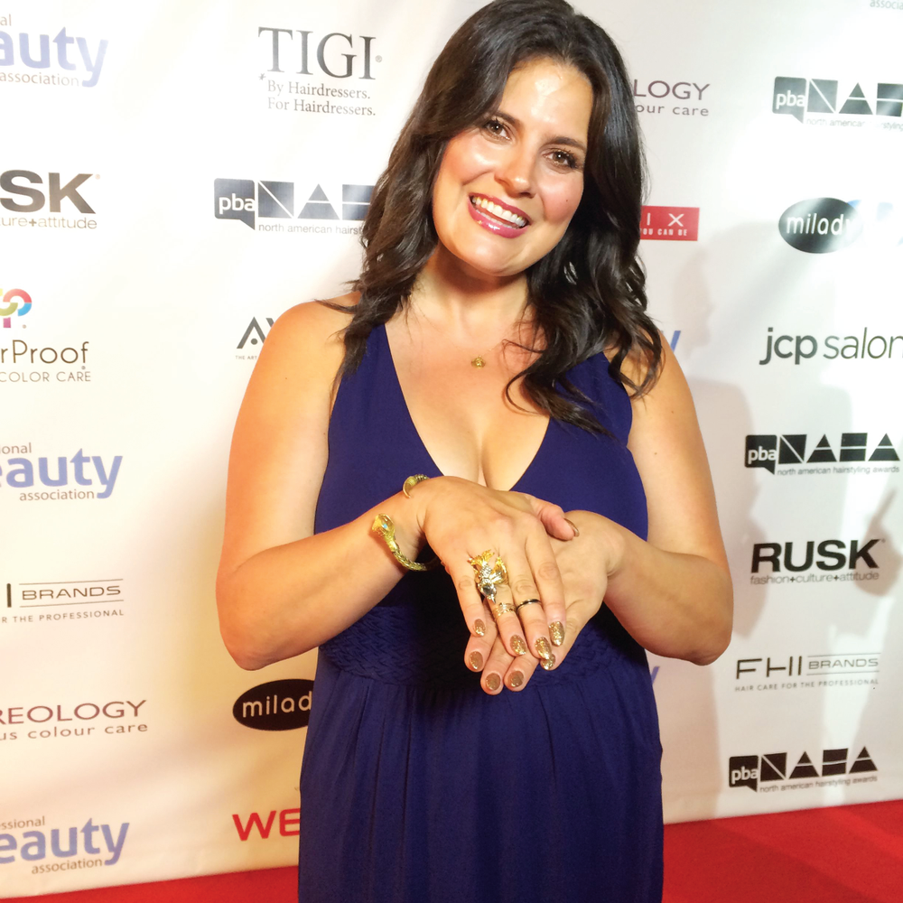 <p>Beauty blogger Dawn McCoy, standing next to the NAILS reporters on the NAHA red carpet, shows off her gold glitter manicure.</p>