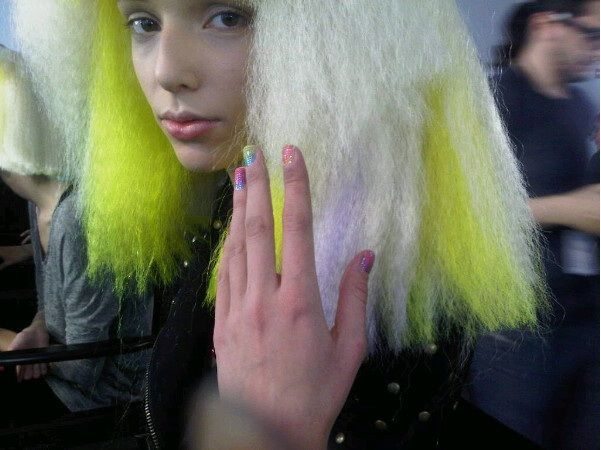 <p>Decked in over-the-top designs, models at the Jeremy Scott Show wore rainbow wigs, light-up jewels on the face, and blue pouts by MAC. Inspired by the concept behind the show, Dashing Diva pro manicurist Pattie Yankee chose <strong>Nail Bliss Bling</strong>&rsquo;s Rainbow appliqu&eacute; to finish the look.</p>