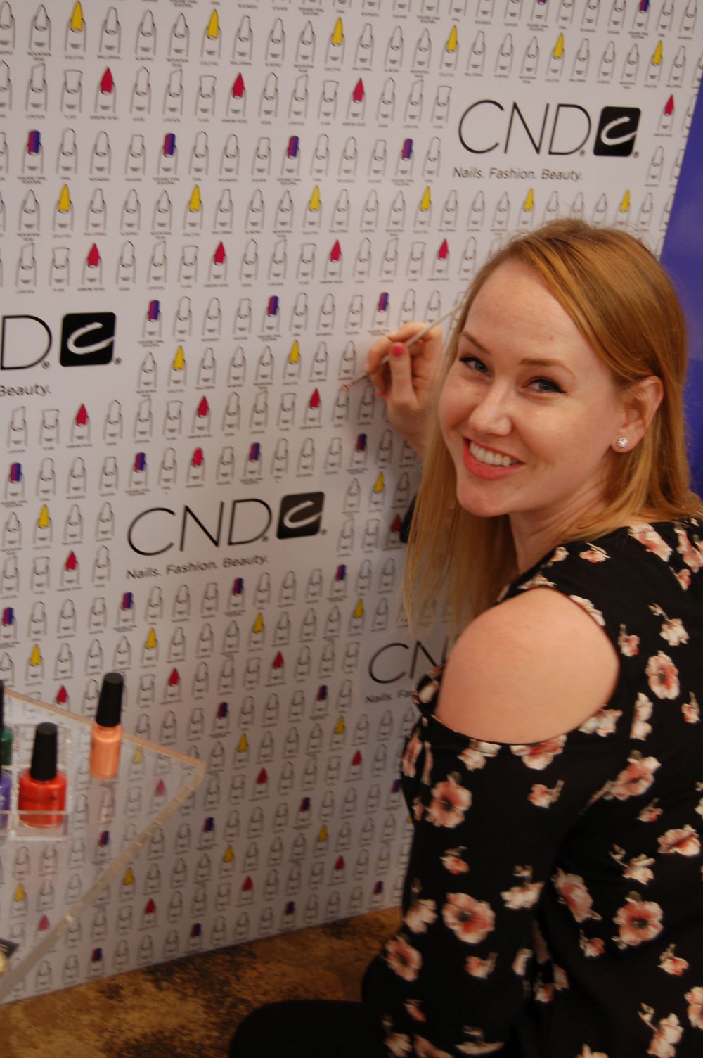 <p>NAILS sales rep Shannon Rahn adding an ombre nail to the CND booth</p>