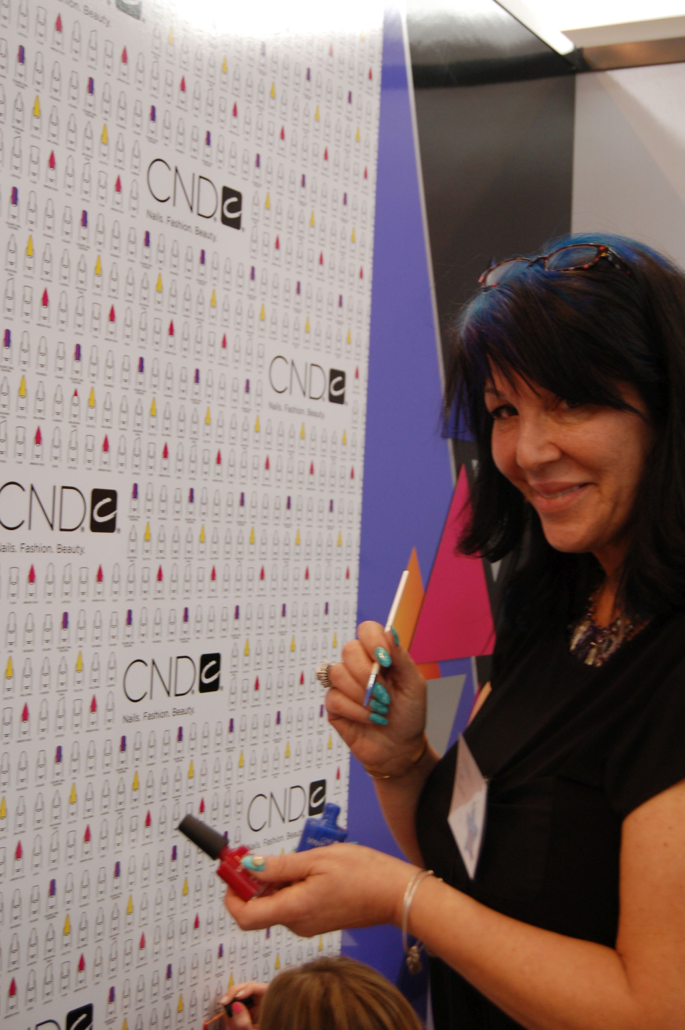<p>Athena Elliott using Vinylux to polish the CND booth</p>