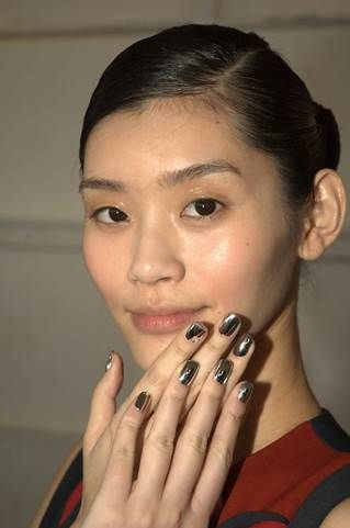 <p>Pattie Yankee created mirror nails by applying glue tabs to the back of press-on nails and adhering them to models for the Delpozo show. Nails were then filed down to a natural length with a rounded shape.</p>