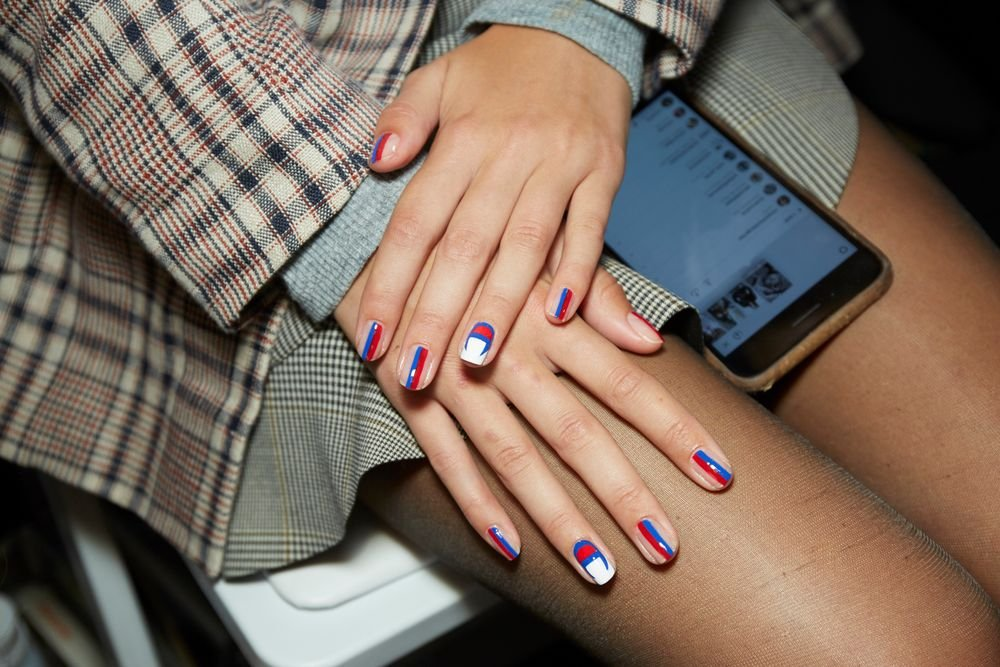 <p>Alicia Torello for Essie used red, navy, gray, cream, and shearling to create a sporty nail design.</p>
