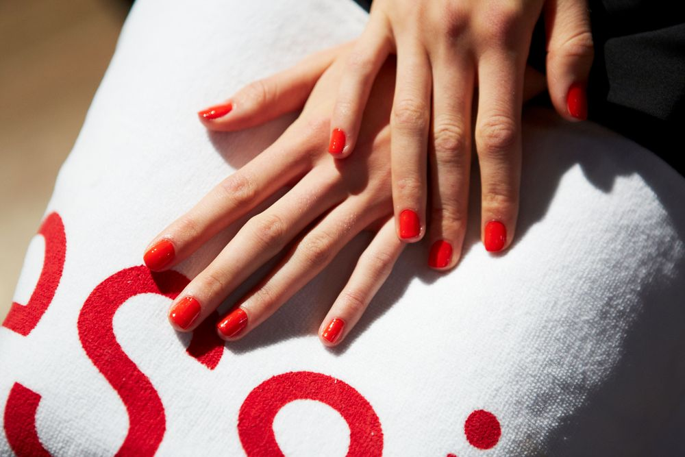 <p>To complement the rainbow colored collection at Jenny Packham, Michelle Saunders for Essie created a youthful red-orange nail. Photo courtesy of Essie.&nbsp;&nbsp;</p>