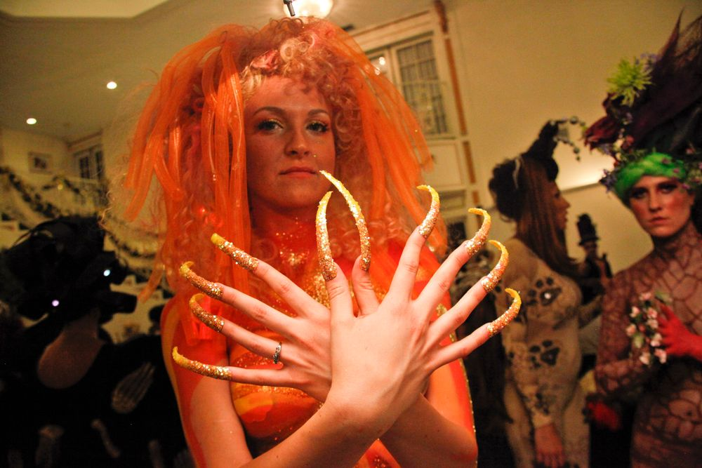 <p>Headliners Salon: Yavenue used four nail tips on each nail for length, then shaped them to a point for a beam effect. She faded five different shades of glitter for a red to bright yellow effect.</p>