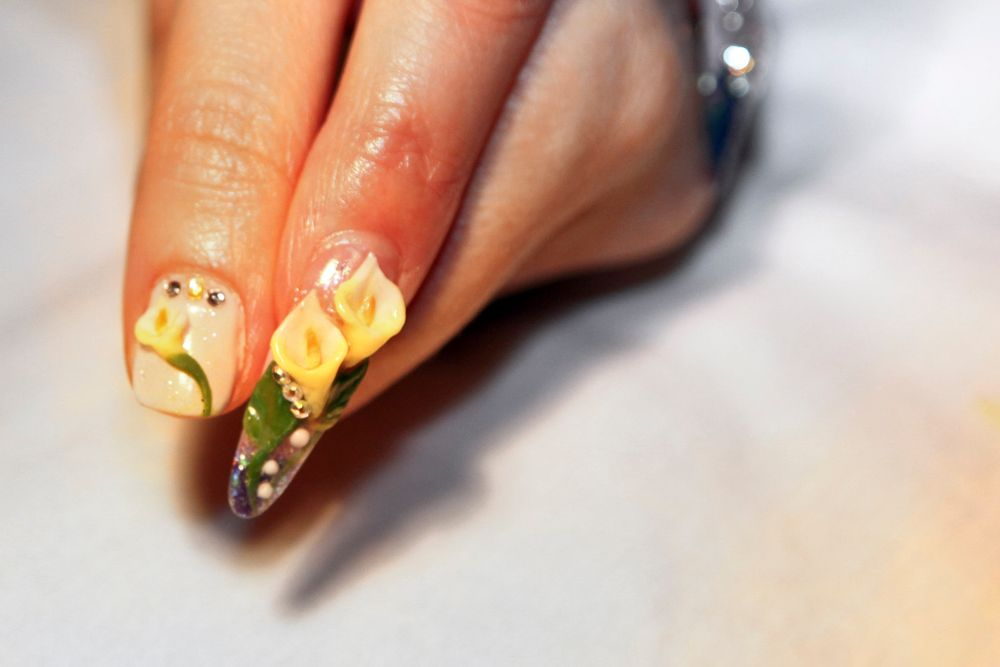 <p>Beautiful Nails educator Ann Chang sculpted this cute calla lily on Cazorla's nail (left nail). Chang had the same style on hers.</p>