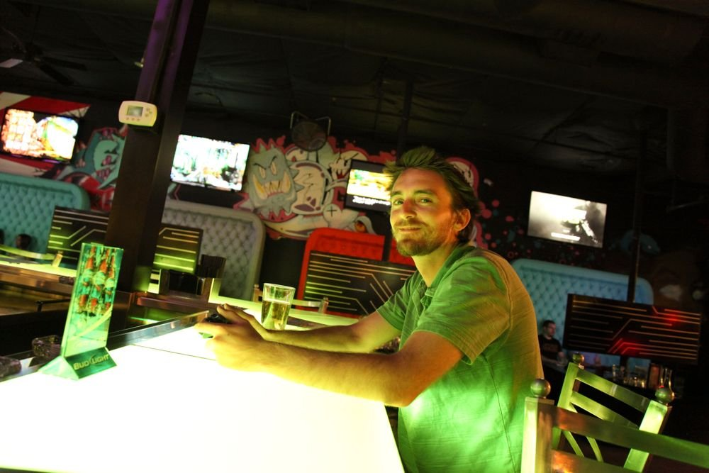 <p>NAILS senior editor Tim Crowley played video games at the bar. Console video game booths line one side (behind him), old school arcade machines line the other.</p>