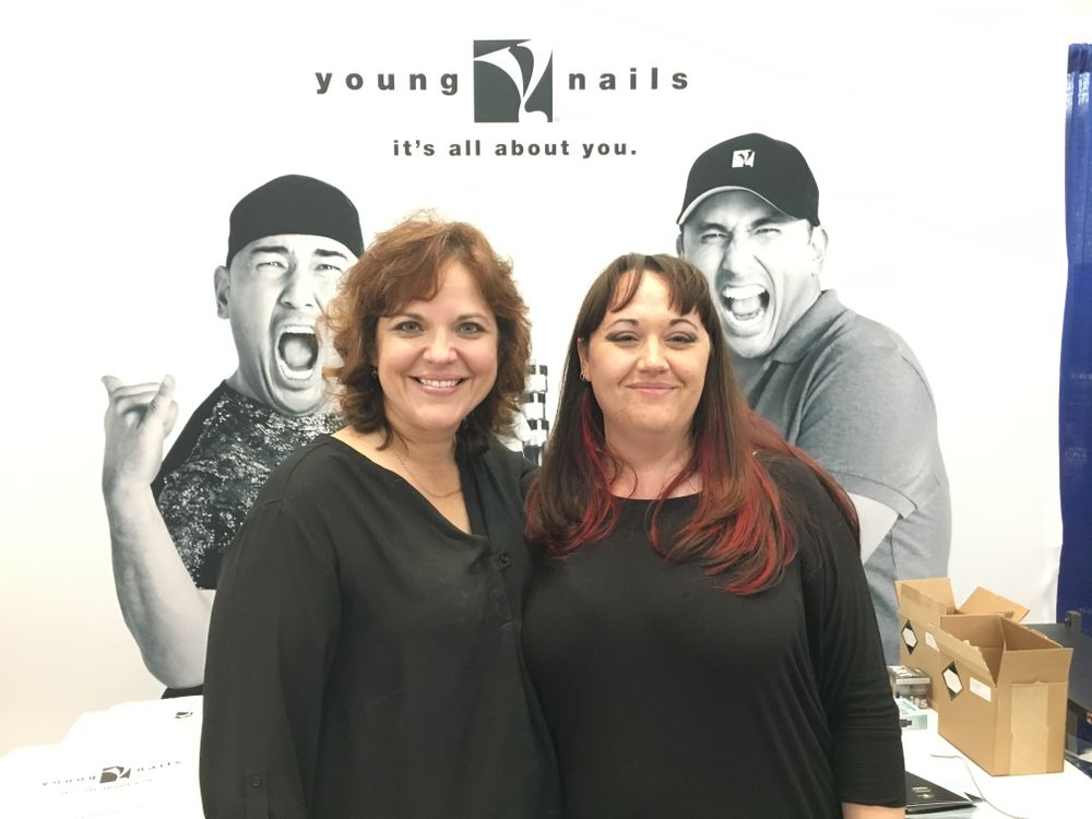 <p>Young Nails' Teresa Carter (left) and Katie Lee demonstrated how to use SlickPour, the brand's new powder coat system.&nbsp;</p>