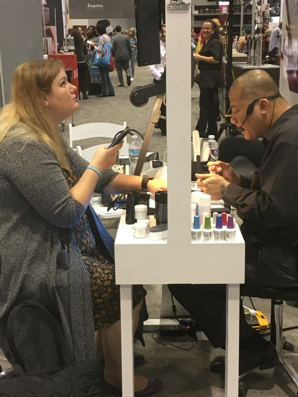 <p>Blogger Krystal Emery getting a PolyGel demo from Vu Nguyen</p>