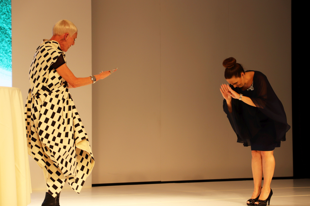 <p>Jan Arnold and Tracey Lee playfully greet eachother on stage</p>