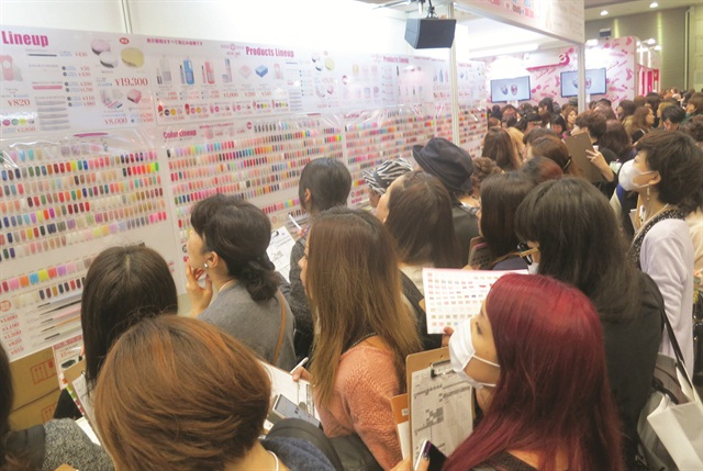 <p>Tokyo Nail Forum shoppers with clipboards gather to see the posted color selection. Photo courtesy @HiJeanJean </p>