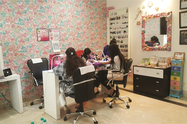 Nail techs work on clients at Nails By Gunjan. Facing a shortage of qualified techs, the owner has started a training academy to help fill the void.