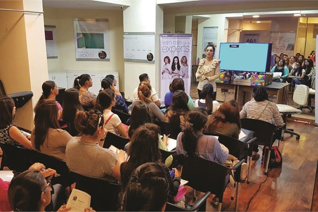 <p>Kavita Kader teaches a nail art seminar to Nail Lounge Academy students.</p>
