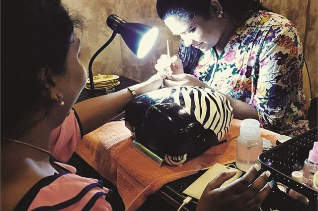 A student practices gel nails at Nail Lounge Academy.
