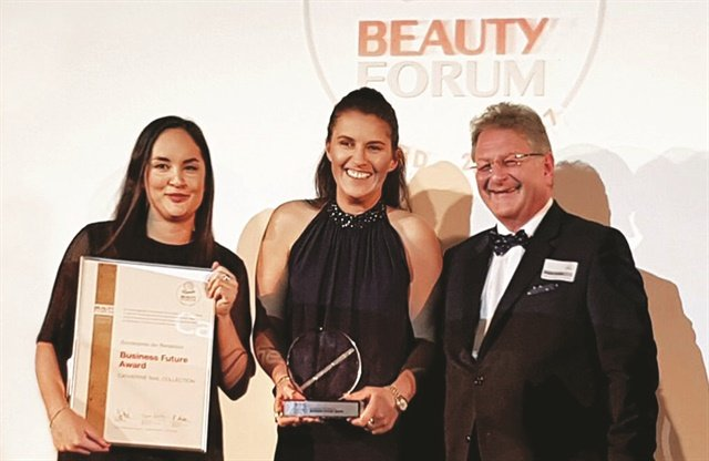 Catherine Frimmel (center) accepts an award on behalf of Catherine Nail Collection at a Beauty Forum ceremony.